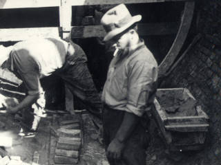 Three men working on an unfinished sewer.
